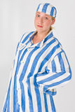 Woman in prison uniform. A studio view of a female wearing a large, blue-striped prison shirt and hat Royalty Free Stock Images