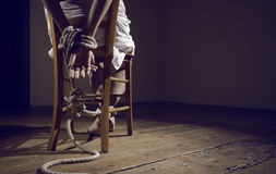 Woman prisoner. Young woman tied to a chair in a empty room Stock Images