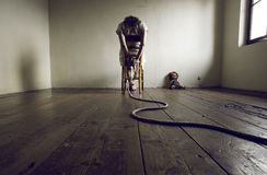 Woman prisoner. Young woman tied to a chair in a empty room Royalty Free Stock Image