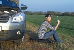 Woman and problem car. Frustrating young woman with wrench near broken car Royalty Free Stock Image