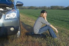 Woman and problem car. Frustrating young woman with wrench near broken car Royalty Free Stock Images