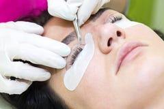 Woman on the procedure for eyelash extensions,. Eyelashes lamination stock photography