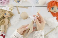 Woman in the process of creating handmade doll, top view, seamstress workplace, many object for needlework, embroidery stock photo