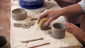 Woman is processing clay detail in workshop, close-up view of hands and table. Female ceramist is making handmade cup in studio. She is preparing details on stock footage