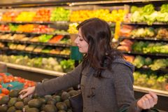 Woman in the produce section of a grocery store. Woman in the produce section of a grocery store stock photography