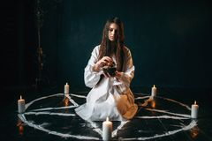 Woman produces a ritual of black magic, occultism. Young woman in white shirt sitting in the center of pentagram circle with candles and produces a ritual of royalty free stock photography