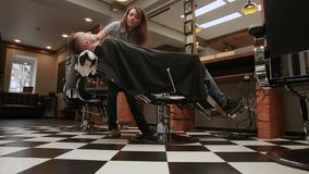 The woman is a professional hairdresser lowers the chair, the camera moves with the help of pristine HD Steadicam stock footage