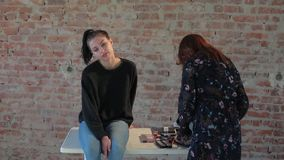 Woman professional makeup artist prepares face of young cute pretty girl for artistic makeup for cinema and creates image. For shooting scene on background stock footage