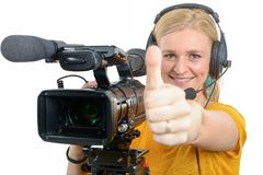 Woman with professional video camera,showing thumb up. A blond young woman with professional video camera, showing thumb up Royalty Free Stock Image