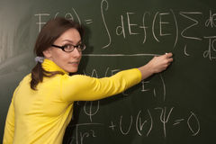 Woman professor teacher student chalk board. Education scene: portrait of an attractive beautiful pretty cute young brown haired caucasian woman (lady, girl royalty free stock photo