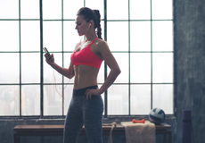Woman in profile listening to music in loft gym Royalty Free Stock Photo