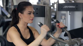 Woman in profile sits on simulator, lifts, shakes hands inside gym stock video footage