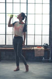 Woman in profile standing in loft gym drinking from water bottle Stock Images