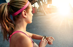 Woman programming her smartwatch before going jogging to track performance Stock Photos