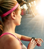 Woman programming her smartwatch before going jogging to track performance Royalty Free Stock Photos