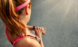 Woman programming her smartwatch before going jogging to track performance Royalty Free Stock Images