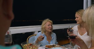 Woman proposing a toast at family dinner. Senior woman proposing a toast during late dinner in outdoor balcony. Family members clanging glasses and having wine stock video