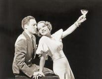 Woman proposing a toast to hesitant man Royalty Free Stock Photos