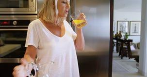 Woman with prosthetic leg drinking orange juice in kitchen 4k. Woman with prosthetic leg drinking orange juice in kitchen at home 4k