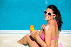 Woman protecting her skin with sunscreen on summer. Woman applying sunscreen or suntan lotion in her shoulder for solar skin protection at swimming pool royalty free stock photo