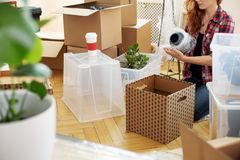 Woman protecting vase with foil while packing stuff into boxes after relocation. Concept stock photography
