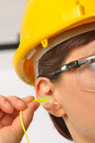 Woman with protective ear plugs Stock Photo