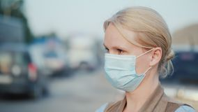 A woman in a protective gauze bandage stands near a dusty dirt road. Environmental problems.  stock video footage