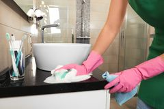 Woman in protective gloves cleaning bathroom. Countertop with sponge, closeup royalty free stock photo