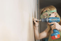 Woman In Protective Goggles Drilling Wall Stock Images