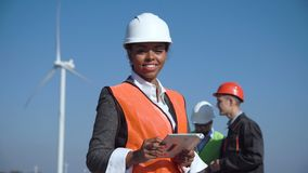 Woman with protective helmet against wind turbine. Female engineer wearing hardhat standing with digital tablet against other engineers and wind turbine on sunny stock video footage