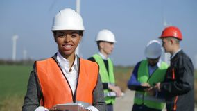 Woman with protective helmet against wind turbine. Female engineer wearing hardhat standing with digital tablet against other engineers and wind turbine on sunny stock footage