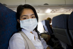 Woman with protective mask in a plane Royalty Free Stock Images