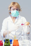 Woman in protective mask tests apple specimen in chemical lab Stock Images