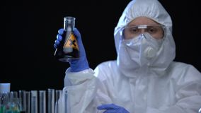 Woman in protective suit holding flask with dark harmful fluid, waste disposal