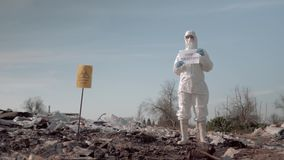 Woman in protective suit and mask holding poster with stop pollution slogan at garbage dump near sign biological hazard stock video