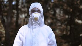 Woman in protective uniform and mask forest, exclusion zone, ecological crisis