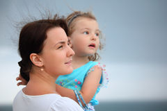 Woman protects girl from wind on seacoast Royalty Free Stock Photography