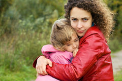 Woman protects little girl from wind in garden Royalty Free Stock Photography