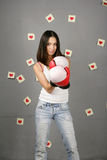Woman protects love. Woman in red boxing gloves. On a background on a wall stickers with the drawn red hearts Royalty Free Stock Photo