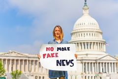 Protester holding sign no more fake news in hands. Woman protest in front of the USA capitol in Washington holding sign saying no more fake news protesting royalty free stock images