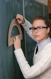 Woman with protractor to the blackboard Stock Photography
