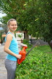 Woman pruning shrub with tool in garden Stock Photo