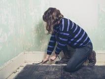 Woman prying nail with crowbar Stock Photos
