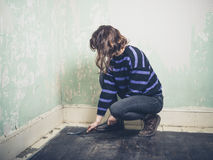 Woman prying nail with crowbar Stock Images