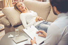 Woman at the psychologist. At the psychologist. Beautiful young women is lying on couch and talking while doctor is making notes royalty free stock images