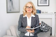 Woman psychologist portrait sitting at casual home office holding organizer. Middle-aged woman psychologist sitting at casual home office wearing eyeglasses stock photo