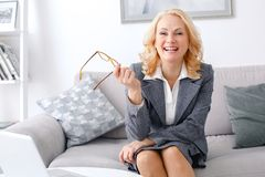 Woman psychologist portrait sitting at casual home office laughing cheerful. Middle-aged woman psychologist sitting at casual home office holding eyeglasses stock images
