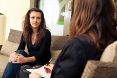 Woman At Psychotherapist. A young women is talking to her therapist Stock Images