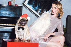 Woman with pug in santa hat Stock Photography