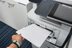 Woman pull paper from the printer. Pull paper from the printer in the office Royalty Free Stock Photography